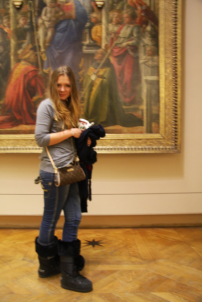 fashionable girl standing infront of a painting in the louvre in paris