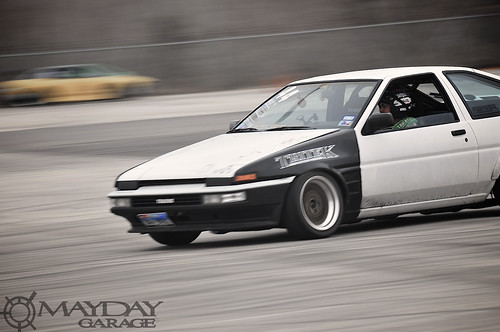 A kouki kitted AE86 drift car sliding through turn 2.