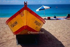 Close Up Frontal View of a Colorful Boat on a Caribbean Beach, Puerto Rico (George Oze) Tags: travel beach horizontal landscape fun colorful bright puertorico relaxing scenic nobody tropical caribbean fishingboat fujivelvia aguadilla caribbeanbeach beachumbrella yellowboat crashboatbeach brightlypainted blurredoutbackground frontalviewofaboat