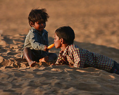 Sharing is caring.. and it sure is enlightment of higher level (Mimor) Tags: sunset people copyright india cute love ice beach childhood canon photography kid sand mine photographer goa expressions games pop pole lolly danny sharing usm icy care dslr drama miramar tender popsicle maximus icey dinesh tlc kumar kartiv 40d primeart mimor sidnid anjaanasafar primefineart dannymaximus fotocrafter dmaximus anjaanarahi