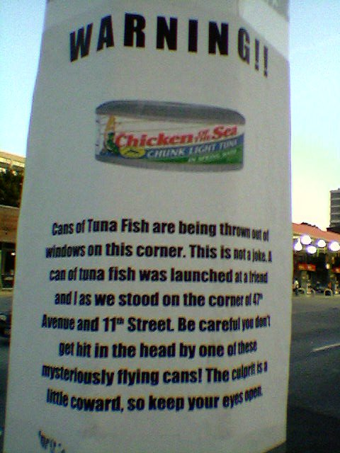 WARNING: Cans of tuna fish are being thrown out of windows on this corner. This is not a joke. Cans of tuna fish are being thrown out of windows on this corner. This is not a joke. A can of tuna fish was launched at a friend and I as we stood on the corner of 47th Avenue and 11th Street. Be careful you don't get hit in the head by one of these mysteriously flying cans! The culprit is a little coward, so keep your eyes open.