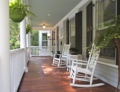 Porch with rocking chairs, hanging baskets, and columns.