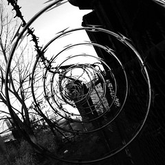 Swirl of Barbed Wire 2 (kristenleigh22) Tags: urban bw white black abandoned philadelphia contrast fence circle spiral reading wire decay viaduct sharp chain link swirl barbed confusion
