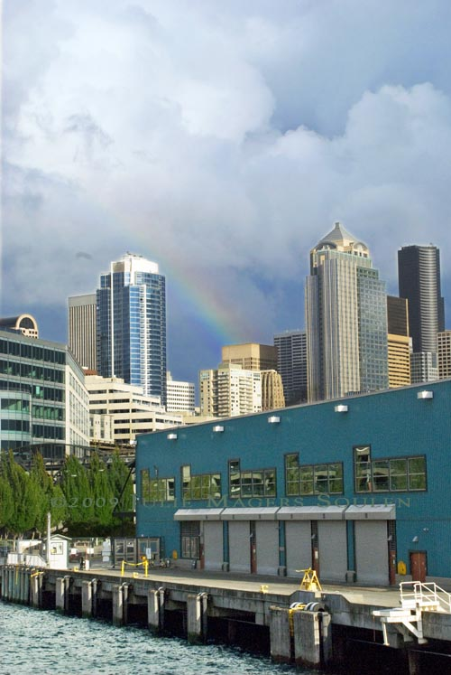 photograph of the Seattle waterfront with a rainbow over downtown