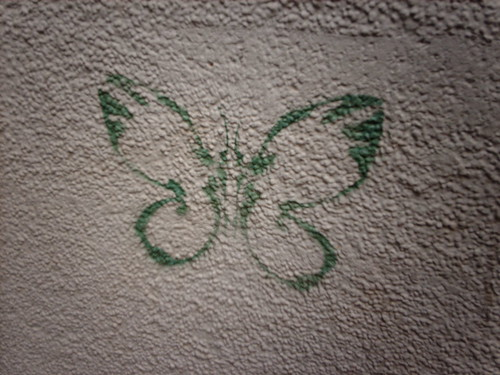 stencil graffiti of a green butterfly