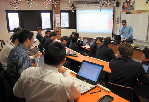 Students in lecture hall with smart blackboard and instructor taking questions on laptops at St. Andrew's College in Aurora Ontario