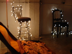 The Trash Talk Exhibit (nytc) Tags: shadow art lowlight christmaslights lantern barstools suitcase
