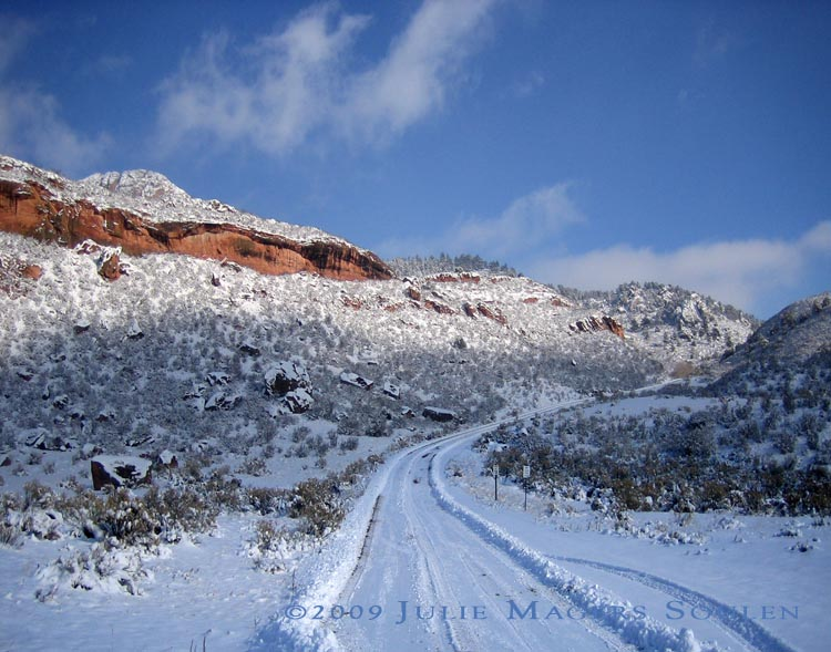 A narrow mountain road disappears up into the Rocky Mountains of northern Colorado on a winter day after the road has been freshly plowed.