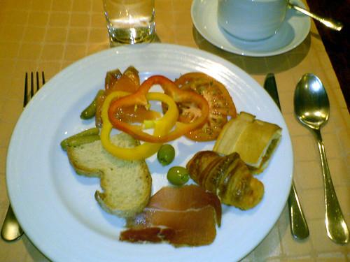 Brød, cornichons, røget laks, tomat, peberfrugt, oliven med ansjoser, empanada, croissant og skinke