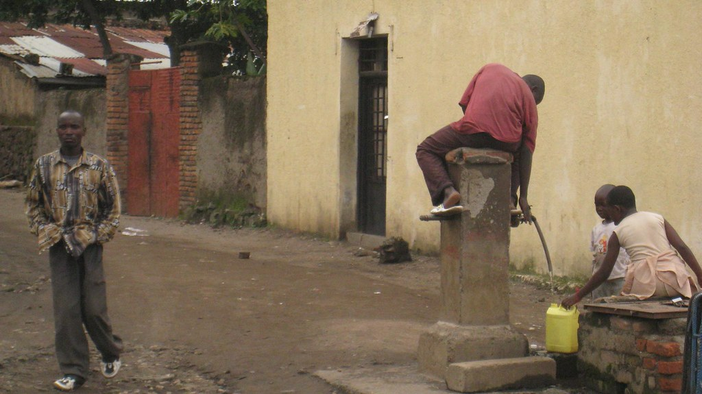 A guy atop a well helps others collect water.
