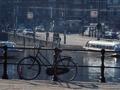 Amsterdam: Bike and Boats (AntyDiluvian) Tags: holland water netherlands dutch amsterdam bike bicycle fence boat canal thenetherlands dew raining tourboat 5photosaday