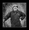Portrait of a hiker (andzer) Tags: autumn portrait people bw white mountain man black cold smile hat pose nikon bokeh coat scout andreas explore stick hiker 2009 zervas andzer wwwandzergr