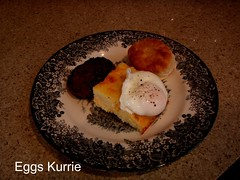 white poached egg on yellow grits with biscuit and sausage patties