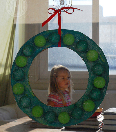 ping pong ball holiday wreath hanging from a window