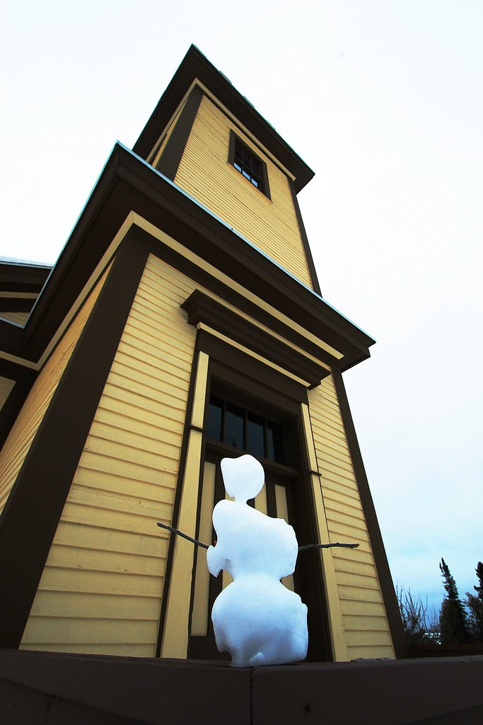 A snowman built in front of a small church.