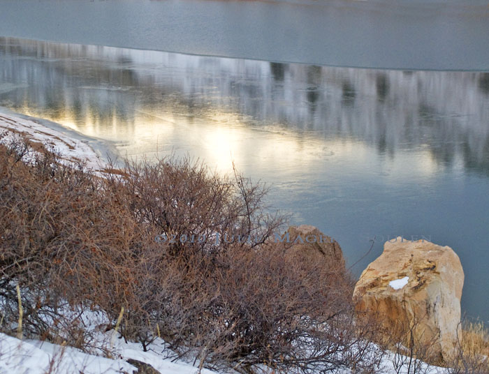 A hillside covered in Mountain Mahogany drops steeply to an ice covered lake reflecting the setting sun.
