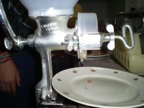 Primer pedacito de carne molida que sale de la máquina