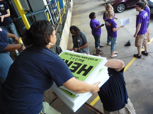 Volunteers from Kohl's load signs that advertise USDA summer meals for kids into their cars at the loading dock of Wisconsin's largest food bank.