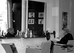 AT THE HAIRDRESSER'S (Akbar Simonse) Tags: street people urban bw holland blancoynegro netherlands reflections mirror zwartwit candid spiegel streetphotography denhaag bn thehague streetshot throughthewindow straat weerspiegeling reflectie kapper kapsalon haidresser straatfotografie straatfoto akbarsimonse