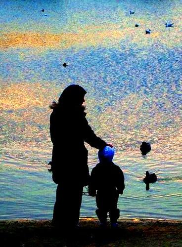 mère et enfant au bord de l'eau le soir