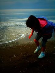 波打ち際で遊ぶムスメ