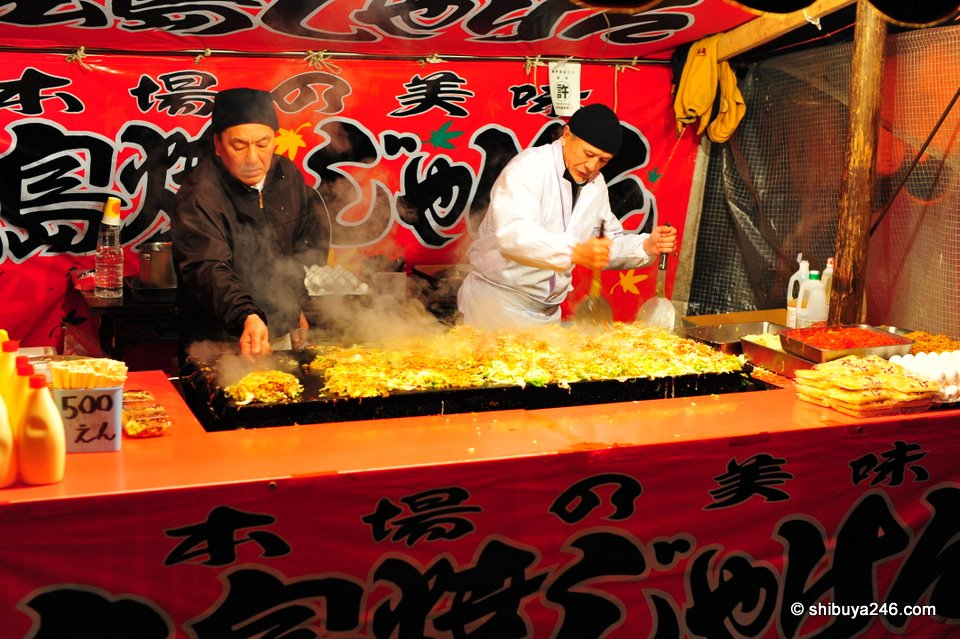 The Okonomiyaki chefs cook up a large hot plate full of food.