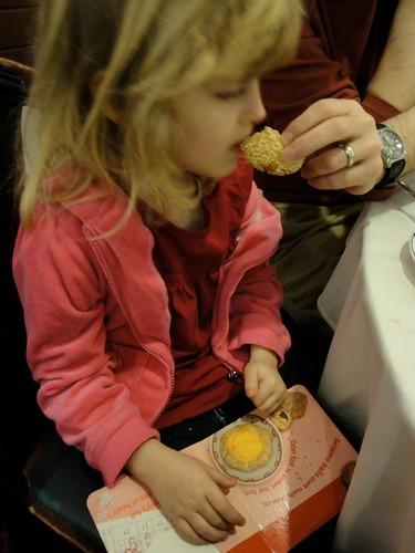 The girl picking at a sesame ball while reading Yum Yum, Dim Sum