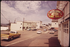 small town quiet street with a few vehicles and a sign reading 'Cathlamet Fire Hall'