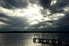 """""""One of these days the sky's gonna break.."""" (aubrey_54) Tags: blue sky sun lake storm nature water clouds outdoors gold dock sony navy tires upnorth beams lightbeams lightstreaks civiltwilight nex3 sonynex3"""