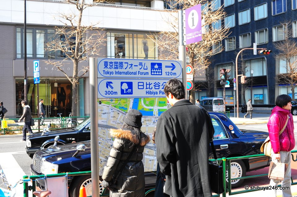 Some people looking for directions outside Yurakucho Station. You can see the big green area on the map here is part of the gardens and start of the Emperor's Palace grounds.