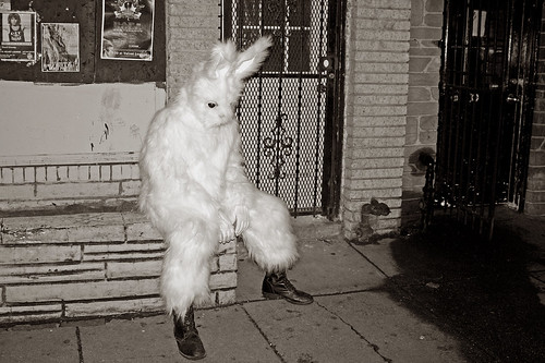 sad rabbit with combat boots sitting in front of a store by IntangibleArts