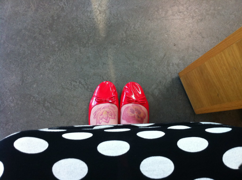 Looking down at a black skirt with white dots and red shoes