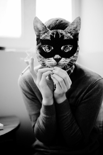Person holding a cat mask in front of their face.