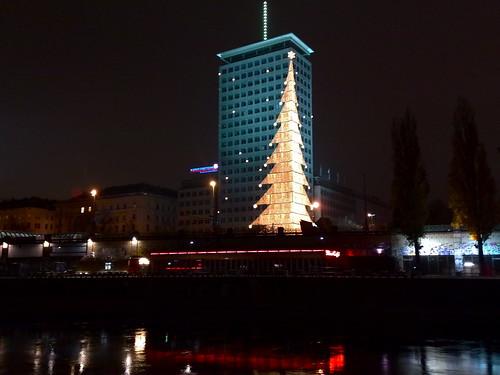 Flex am Donaukanal bei Nacht, darüber Fassade mit Lampendekoration in Christbaumform