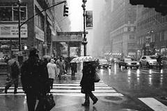 new york city snow storm (ho_hokus) Tags: nyc bw snow newyork monochrome umbrella olympusstylusepic taxi streetphotography snowing 28 badweather xp2super blackandwhite35mmfilm ilfordxp2s ny2010