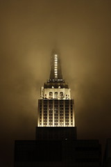Empire in the clouds. (Maurizio Contini) Tags: ocean park street new york city nyc travel bridge windows light vacation sky people panorama horse woman usa holiday ny storm reflection building window water car statue skyline architecture brooklyn clouds america skyscraper river garden dark square liberty island pier us iron artist pattern state geometry walk alice manhattan united north central broadway dramatic police nypd atlantic east madison empire hudson states mm crosswalk avenue wonderland 5th flatiron nord fifth maurizio rockfeller contini