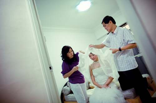 Father and Mother putting on the wedding veil for the bride