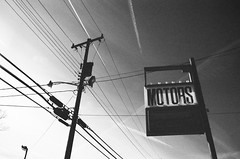Motors and Stuff (shiphome) Tags: blackandwhite abandoned film 35mm vintage lightbulbs dirty motors powerlines worn neopan1600 contrails nikonfm2 vacantlot oldsign ushighway70 marionnc