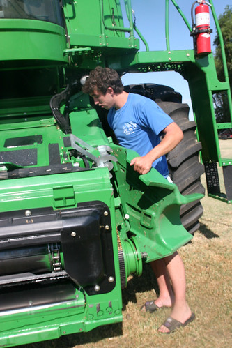 Oak replaces a feeder house cover after the combine has been washed.