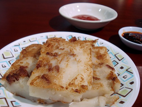Three rectangles of pan-fried radish cake sit on a small plate.  Each rectangle is a little over 1cm thick, white and wobbly on the interior, and with brown marks from frying on the outside.