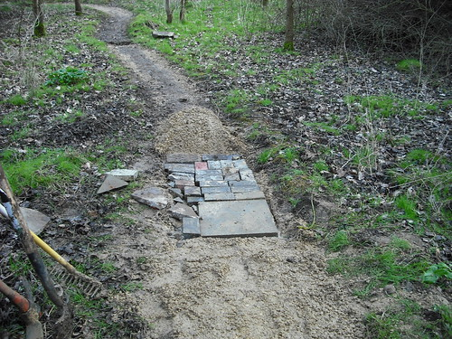 Using concrete slabs and bricks to reinforce trail.