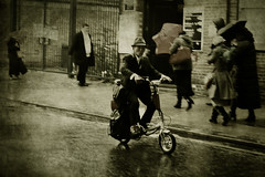 Braving the rain (Che-burashka) Tags: people urban man london hat rain vintage walking driving oldstyle wind chinese fast windy retro hiding cinematic umbrellas bicicle deptford resistance textured badweather londonist 400d locallondon