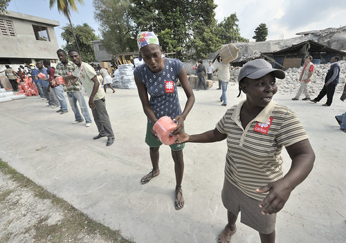 HAITI/QUAKE by Jesuits In The U.S.. Earthquake survivors in the quake-ravaged Haitian city of Leogane unload emergency supplies provided.