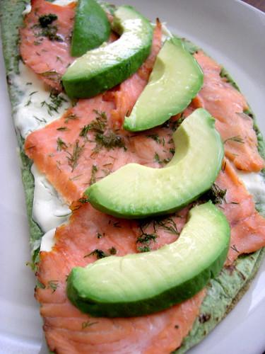 smoked salmon, avocado, creamcheese pizza on a spinach tortilla