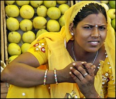 woman selling fruit in Jaipur , India (maios) Tags: world woman india apple girl yellow tattoo fruit lady portraits eyes hands selling jaipur rajasthan maios womansellingfruitinjaipurindia