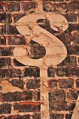 dollar sign painted on some bricks