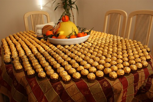 A bunch of Wrapped up Choclate truffles sitting on a table