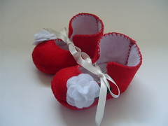 red and white baby girl booties with flower motifs