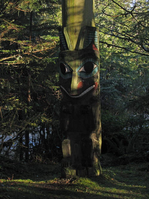 a totem catches some afternoon light through the trees of Kasaan Totem Park, Kasaan, Alaska