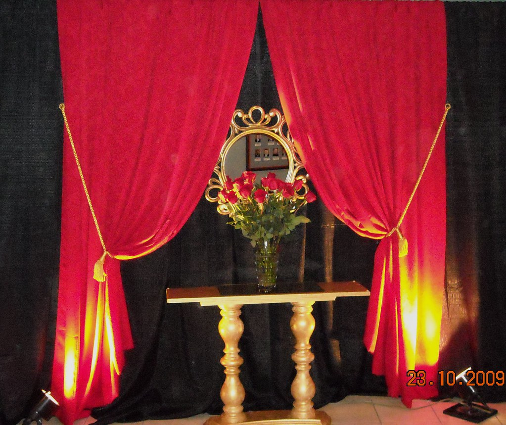 pedistal table with roses and red drape